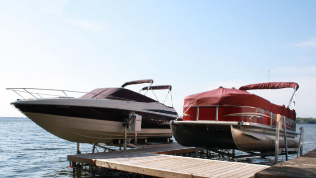 2 boats raised with lift at dock
