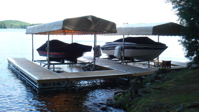 Cantilever boat lifts with roof system and pipe docks
