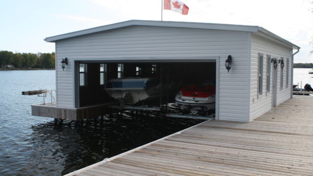 Completed boathouse on pilings with wetslip boat lifts