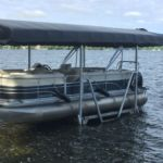 Vertical pontoon boat lift with black canopy